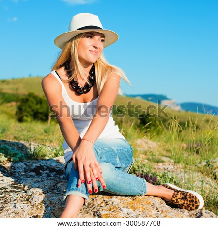 portrait of the attractive, slender, beautiful young Caucasian  blonde girl in a stinny hat.Smiling girl enjoys fine warm sunner weather highly in mountains. instagram style - stock photo