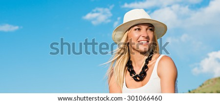 portrait of the attractive, slender, beautiful young Caucasian  blonde girl. Smiling girl enjoys fine warm sunner weather highly in mountains against the sea - stock photo