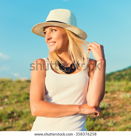 portrait of the attractive, slender, beautiful young Caucasian  blonde girl. Smiling girl enjoys fine warm summer weather. Photo with instagram style filters