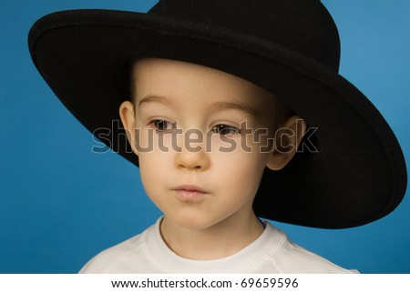 Portrait of the baby in a big black hat - stock photo