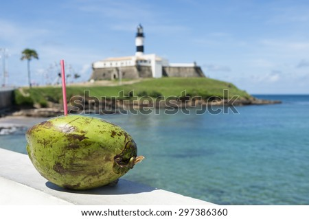 Portrait of the Barra Salvador Brazil lighthouse from the promenade balcony with a green drinking coconut in the foreground - stock photo