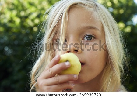 Portrait of the beautiful blond girl eating an apple outdoors - stock photo
