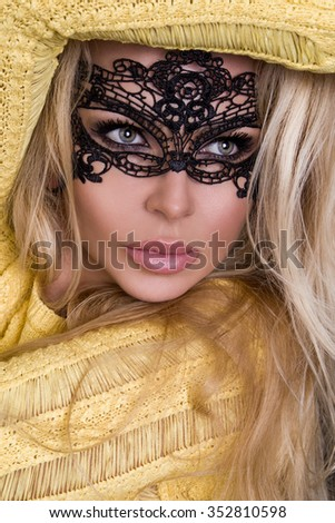 Portrait of the beautiful blond hair sexed women of Young girl model in a black mask carnival ball in tight elegant dress in yellow on a black background