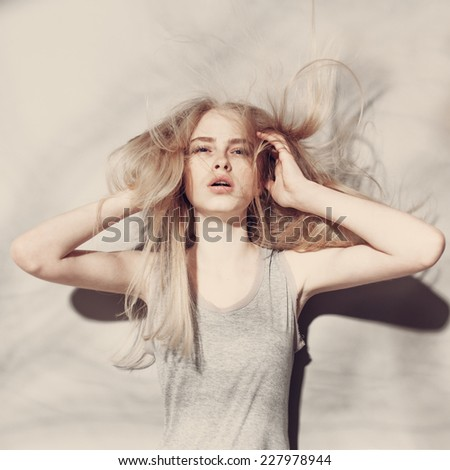 Portrait of the beautiful blonde girl in studio with long hair - stock photo