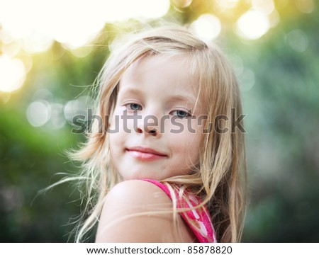 Portrait of the beautiful blonde little girl on nature
