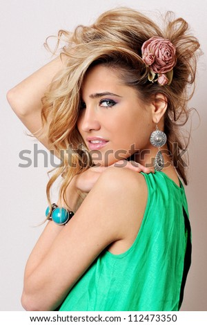 Portrait of the beautiful blonde woman in green dress. Studio shoot. - stock photo