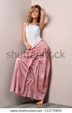 Portrait of the beautiful blonde woman in pink skirt. Studio shoot.
