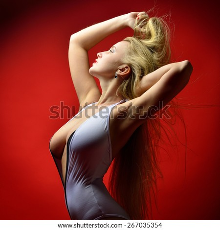 Portrait of the beautiful blonde  woman in white lingerie in studio with red background - stock photo