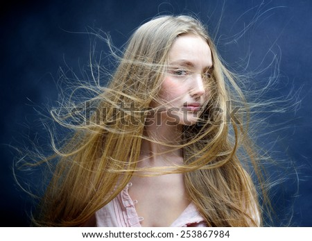 Portrait of the beautiful blonde woman with flying long hair. She is in studio . - stock photo