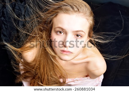 Portrait of the beautiful blonde woman with flying long hair. She is with naked shoulders  in studio . - stock photo