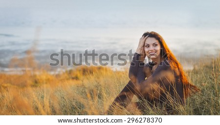 Portrait of the beautiful brunette woman at the windy autumn day relaxing on coast feeling good - stock photo