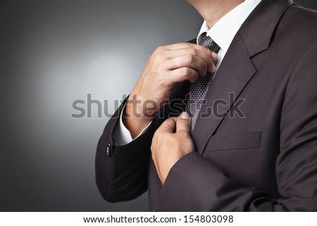 portrait of the beautiful businessman in black costume tie one's necktie - stock photo