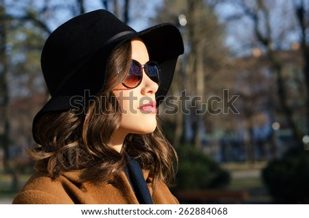 Portrait of the beautiful fashionable girl outdoor on sunny spring day. - stock photo