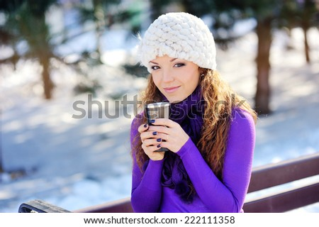 Portrait of the beautiful girl drinking hot beverage in snowy winter.