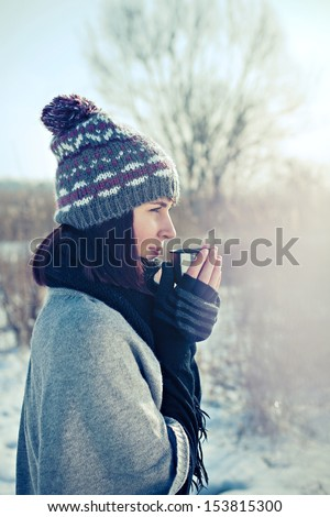 Portrait of the beautiful girl drinking hot tea in snowy winter - stock photo