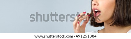 Portrait of the beautiful girl eating chocolate cookies isolated on gray background.
