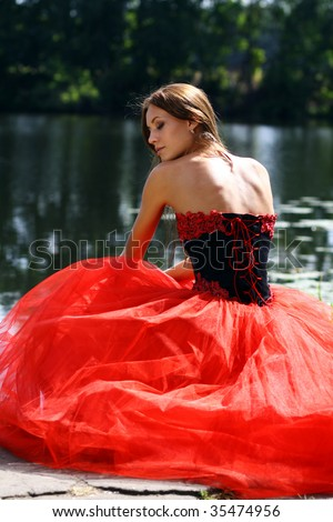Portrait of the beautiful girl in a red ball dress