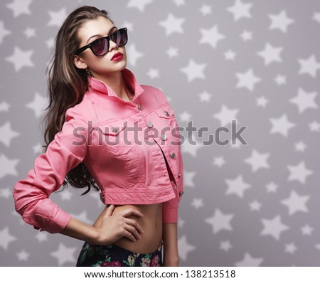 portrait of the beautiful girl in dark glasses on a gray background with stars - stock photo