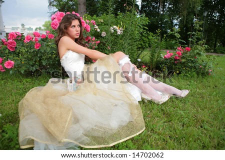 portrait of the beautiful girl in luxurious white-golden gown on background of the rosebush