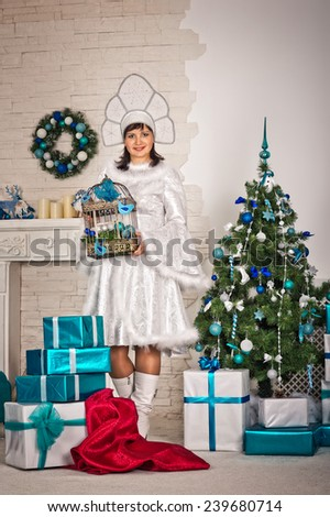 Portrait of the beautiful girl in the New Years dress with gifts.