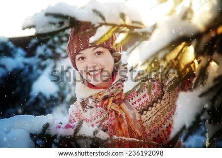 Portrait of the beautiful girl near a fir-tree in the winter wood - stock photo