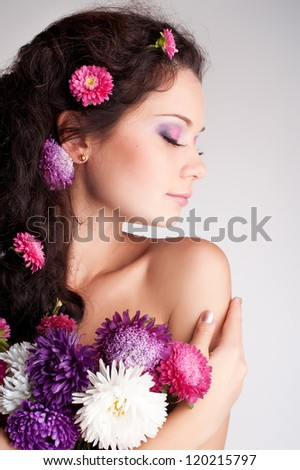 Portrait of the beautiful girl on a grey background with flower chrysanthemum