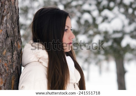 Portrait of the beautiful girl on snowy winter day.   - stock photo