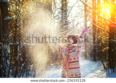 Portrait of the beautiful girl throwing snow in the winter wood - stock photo