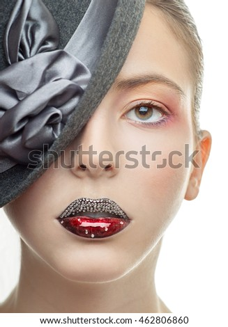 Portrait of the beautiful girl with a red lipstick in a black hat