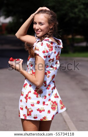 Portrait of the beautiful girl with a strawberry - stock photo