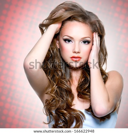 Portrait of  the  beautiful girl with  long curly hairs posing at studio and looking at camera - stock photo