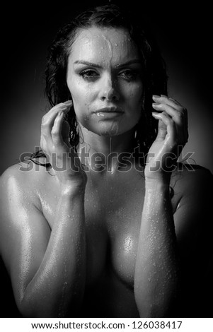 Portrait of the beautiful naked woman at which the water flows, on a gray background.