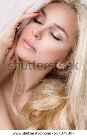 Portrait of the beautiful sensual blonde woman with perfect natural and smooth face in a delicate makeup no makeup