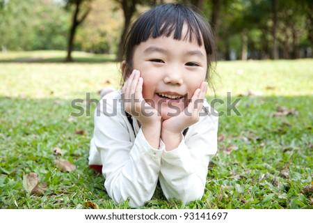 Portrait of the beautiful small Asian girl/park scene - stock photo