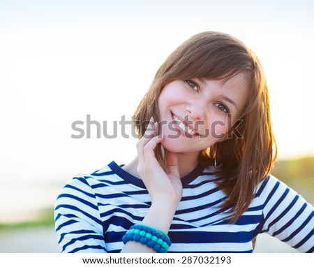 Portrait of the beautiful teen girl with fluttering hair near the sea