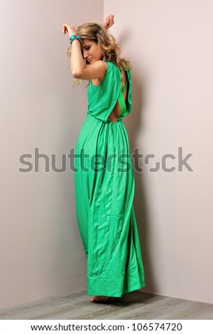 Portrait of the beautiful woman in a long green dress. Studio photoshoot. - stock photo
