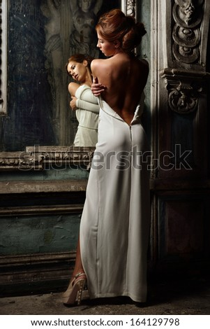 Portrait of the beautiful woman in white dress with naked back. She is standing at the mirror. Studio with interior of old palace. Not necessary property release.