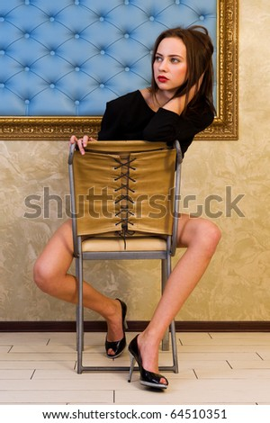 Portrait of the beautiful woman. She is sitting on the chair