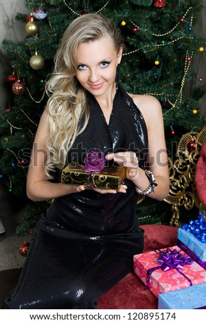 Portrait of the Beautiful woman with gift box at the Christmas tree.