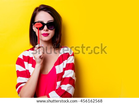 portrait of the beautiful yound woman with lip shaped toy on the yellow background