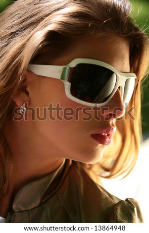 portrait of the beautiful young brunette in big sunglasses, close-up