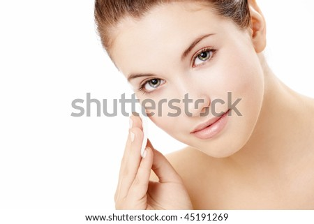 Portrait of the beautiful young girl applying on a face a cosmetic pad, isolated - stock photo
