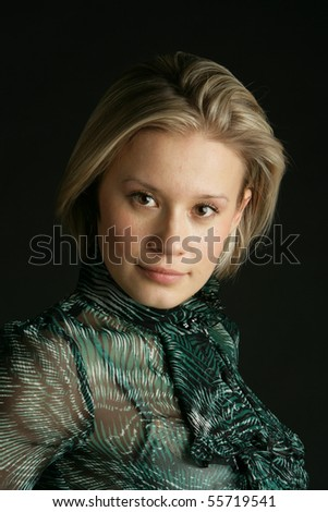 Portrait of the beautiful, young girl-blonde in a green transparent blouse