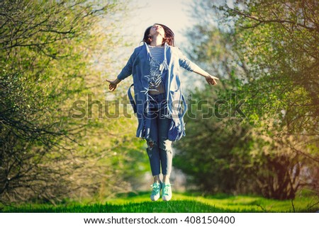 portrait of the beautiful young woman jumping in the park