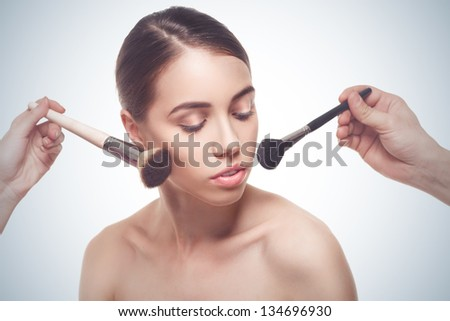 Portrait of the beautiful young woman making make-up isolated