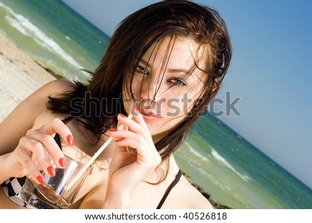 Portrait of the beautiful young woman on a beach - stock photo