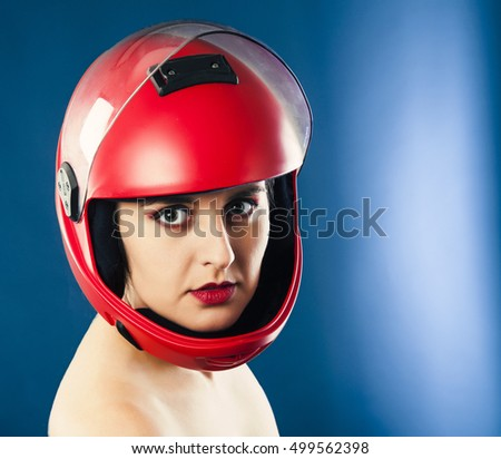 Portrait of the beautiful young woman parachutist with red lips in red helmet on blue background, studio shot