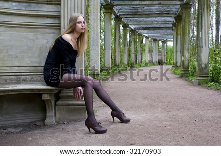 Portrait of the beautiful young woman. She is sitting in the old garden