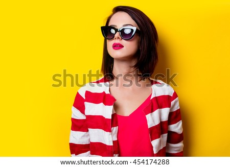 portrait of the beautiful young woman standing on the yellow background