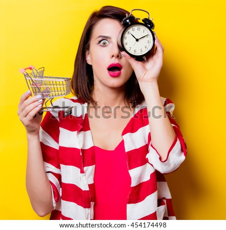 portrait of the beautiful young woman with cart for shopping and black alarm clock on the yellow background - stock photo